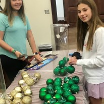 OPYC member Grace Toman works on ornaments with Cheney Davidson