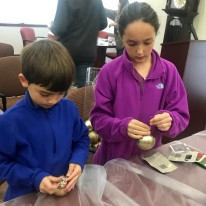 Ike Davidson and Maeve McGregor work steadily to string city's new Christmas ornaments