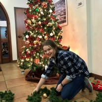 Sophia Lathrop carefully working greenery to surround base of Olmos Park City Hall tree
